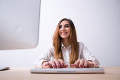 Smiling young woman typing on the keyboard Stock Image