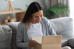 Free Smiling Young Woman Unpacking Parcel, Opening Cardboard Box Stock Photos - 179724873