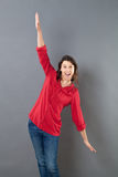 Smiling young woman using arms opened wide to fly Stock Image