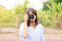 Smiling young woman using camera to take photo outdoors at the park Stock Photography
