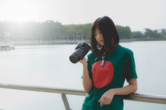 Smiling young woman using a camera to take photo outdoors stock photo
