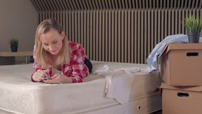 Smiling young woman using her phone in new house stock footage