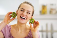Smiling young woman using kiwi slices as earrings Royalty Free Stock Images