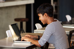 Smiling young woman using laptop at cafe Stock Images
