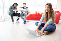 Smiling young woman using laptop on floor Stock Image