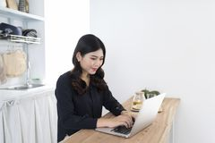 Smiling young woman using laptop in the kitchen at home stock photo