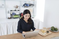 Smiling young woman using laptop in the kitchen at home stock image