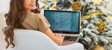 Smiling young woman using laptop near christmas tree. In living room Stock Image