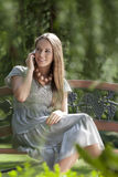 Smiling young woman using mobile phone on park bench Royalty Free Stock Images