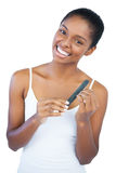 Smiling young woman using nail file Stock Photography