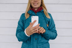 Smiling young woman using smart phone. Woman in blue jacket sending a text message from her cell phone Royalty Free Stock Photos