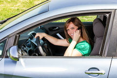 Smiling young woman using smart phone while driving Royalty Free Stock Photography
