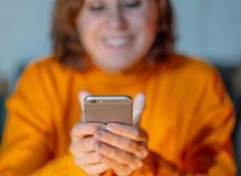 Smiling young woman using smart phone in mobile addiction and online dating royalty free stock photos