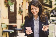 Smiling young woman using smart phone. Smiling young woman using smart phone to check a credit card Royalty Free Stock Image