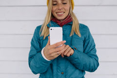 Smiling young woman using smart phone. Woman in yellow knitted hat and a blue jacket sending a text message from her cell phone Stock Photo