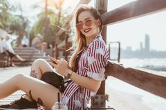 Smiling young woman using smartphone while sitting on pier at beach and looking. At camera royalty free stock images