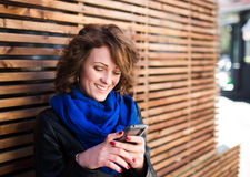 Smiling young woman using smartphone on the street Stock Photography