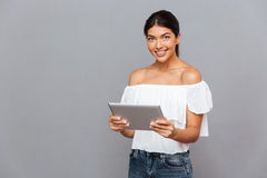 Smiling young woman using tablet computer and looking at camera. Isolated on a gray background Royalty Free Stock Photos