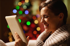Smiling young woman using tablet pc in front of christmas tree Stock Photography