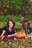 Smiling young woman and the vegetables in autumn park. Smiling pretty young woman lying on the foliage near the vegetables in the autumn park stock photos