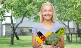 Smiling young woman with vegetables in home garden Royalty Free Stock Photos