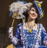 Smiling young woman in the Venice carnival with an elegant blue costume. Smiling masked woman in the Venetian carnival with a blue costume and a blooming hat royalty free stock photo