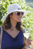 Smiling young woman in vineyard holding glass of white wine. Stock Photos
