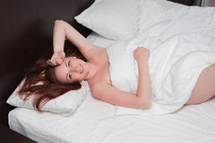 Smiling young woman wakes up on bed royalty free stock photos