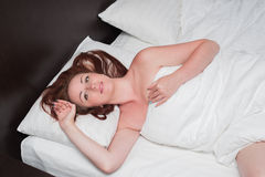 Smiling young woman wakes up on bed stock image
