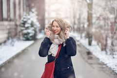 Smiling young woman walking along a snowy road. In winter holding the fur trim on her jacket looking to the side with a happy smile stock photography