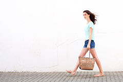 Smiling young woman walking with handbag Stock Image