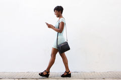 Smiling young woman walking and looking at cell phone Royalty Free Stock Photography
