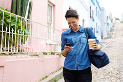 Smiling young woman walking with mobile phone and bag Royalty Free Stock Photography