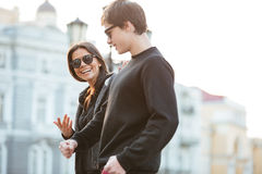 Smiling young woman walking outdoors with her brother. Stock Photos