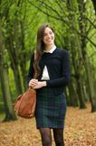 Smiling young woman walking in the park on a autumn day. Portrait of a smiling young woman walking in the park on a autumn day Royalty Free Stock Images