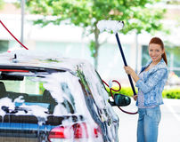 Smiling young woman washing, cleaning her compact car Stock Image