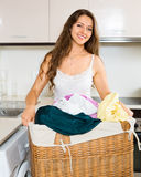 Smiling young woman washing clothes in washer Stock Photos