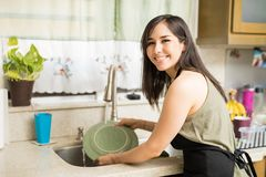 Portrait of a happy woman cleaning utensils in kitchen sink. Smiling young woman washing dishes in the kitchen in front of a window with flowers in pots in the Royalty Free Stock Images