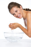 Smiling young woman washing face in glass bowl with water. Isolated on white stock images