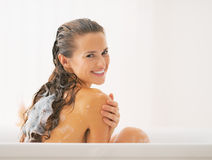 Smiling young woman washing hair in bathtub Royalty Free Stock Images