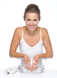 Smiling young woman washing hands in glass bowl with water Stock Photo