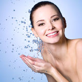Smiling young woman washing her face. Healthy smiling  woman washing her face with clean water Stock Photos