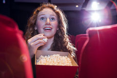 Smiling young woman watching a film Stock Photo