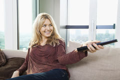 Smiling young woman watching television on sofa at home Stock Photography