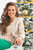 Smiling young woman watching tv in front of christmas tree Royalty Free Stock Images