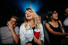 Smiling young woman watching woman in theater. Indoor shot of smiling young women watching women in theater. Group of friends in multiplex cinema Royalty Free Stock Photos