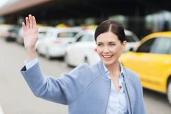 Smiling young woman with waving hand over taxi Stock Photo