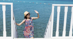 Smiling  young woman waving on a sea background Stock Image