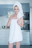 Smiling Young Woman Wearing Bath Towel. Three Quarter Length Portrait of Smiling Young Woman Wearing Bath Towel in Kitchen Stock Photo
