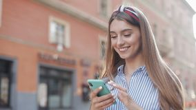 Smiling young woman wearing in blue and white striped dress shirt using smartphone standing on the old street background stock video footage